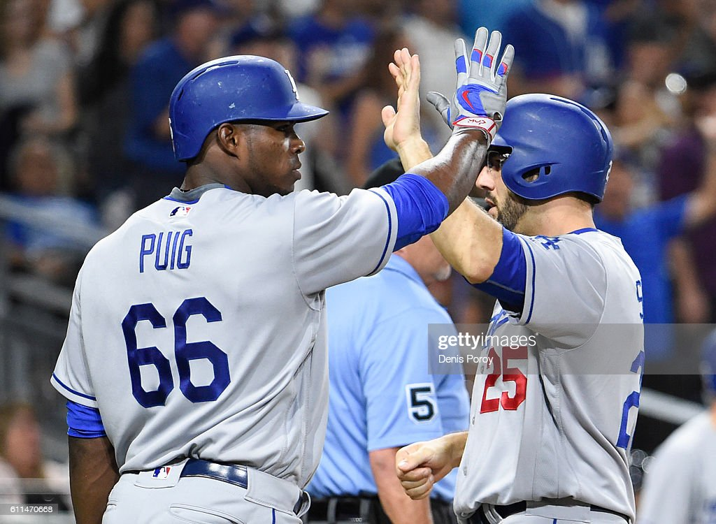 Yasiel Puig #66 of the Los Angeles Dodgers and Rob Segedin #25 hight-five after scoring during the sixth inning of a baseball game against the San Diego Padres at PETCO Park on September 29, 2016 in San Diego, California.