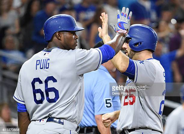 Yasiel Puig of the Los Angeles Dodgers and Rob Segedin hightfive after scoring during the sixth inning of a baseball game against the San Diego...