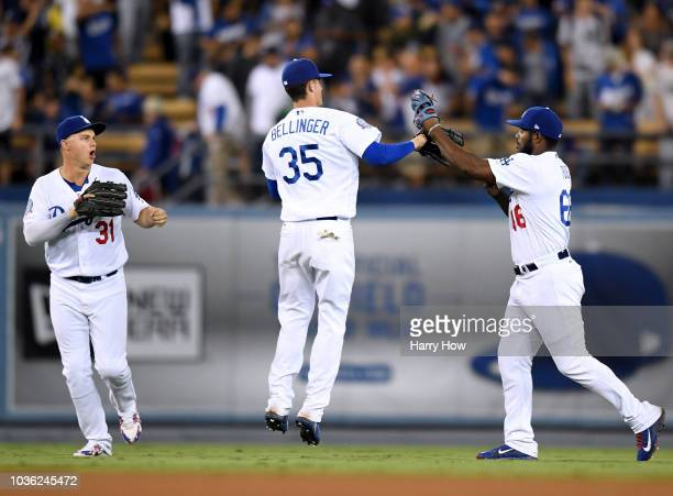 Yasiel Puig of the Los Angeles Dodgers celebrates a 52 win over the Colorado Rockies with Cody Bellinger and Joc Pederson at Dodger Stadium on...
