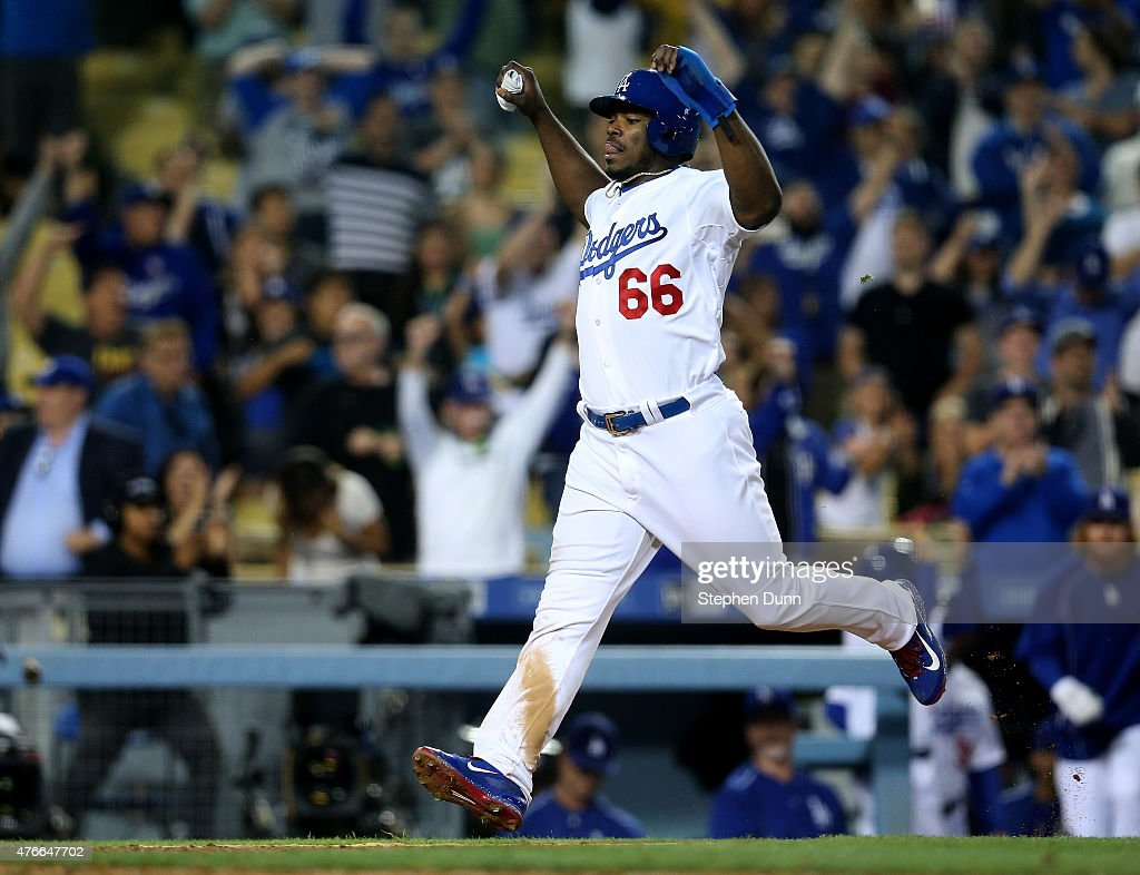 Yasiel Puig #66 of the Los Angeles Dodgers celebrates as he runs home with the winning run on a walk off single by Howie Kendrick in the ninth inning against the Arizona Diamondbacks at Dodger Stadium on June 10, 2015 in Los Angeles, California. The Dodgers won 7-6.