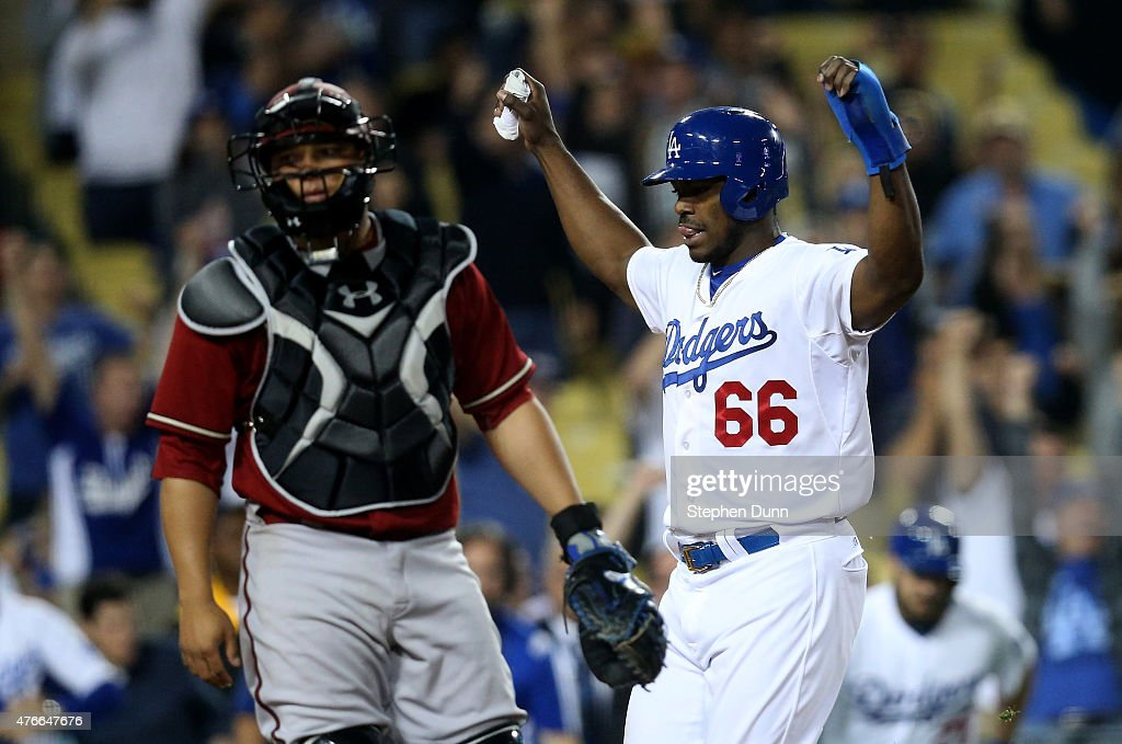 Yasiel Puig #66 of the Los Angeles Dodgers celebrates as he scores the winning run on a walk off single by Howie Kendrick in the ninth inning past catcher Wellington Castillo #7 of the Arizona Diamondbacks at Dodger Stadium on June 10, 2015 in Los Angeles, California. The Dodgers won 7-6.