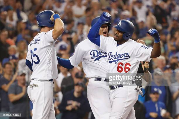 Yasiel Puig of the Los Angeles Dodgers celebrates at home plate with Cody Bellinger and Manny Machado after Puig hit a threerun home run in the sixth...