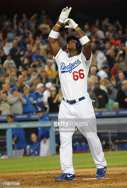Yasiel Puig of the Los Angeles Dodgers celebrates at homeplate after hitting a grandslam homerun in the eighth inning against the Atlanta Braves at...