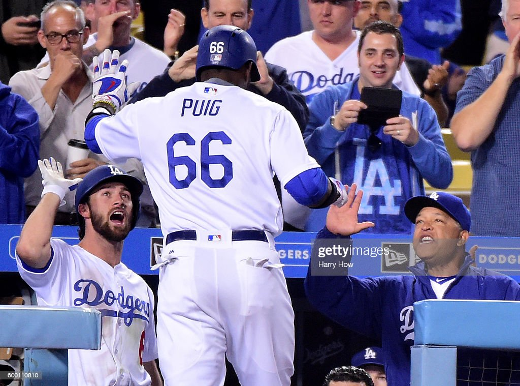Yasiel Puig #66 of the Los Angeles Dodgers celebrates his solo homerun with Charlie Culberson #6 and Manager Dave Roberts #30 to take a 3-1 lead over the Arizona Diamondbacks during the sixth inning at Dodger Stadium on September 7, 2016 in Los Angeles, California.