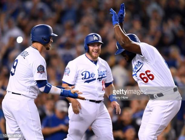 Yasiel Puig of the Los Angeles Dodgers celebrates his three run homerun with Yasmani Grandal and Max Muncy to take a 52 lead over the Colorado...