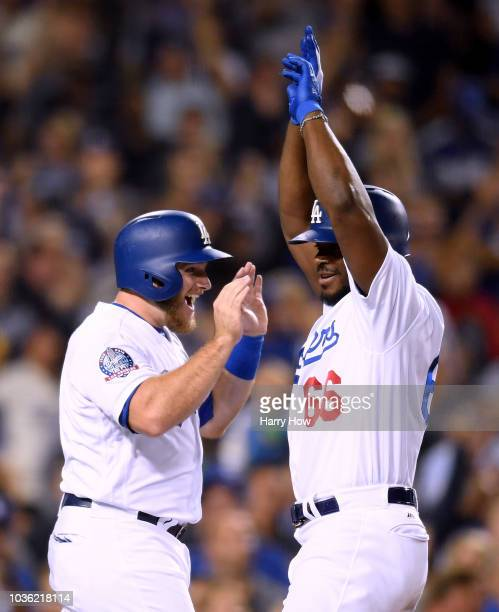 Yasiel Puig of the Los Angeles Dodgers celebrates his three run homerun with Max Muncy to take a 52 lead over the Colorado Rockies during the seventh...