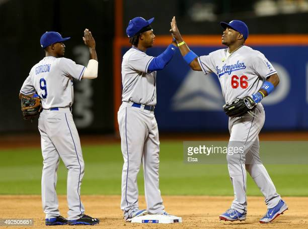 Yasiel Puig of the Los Angeles Dodgers celebrates the win with teammates Hanley Ramirez and Dee Gordon after the game against the New York Mets on...