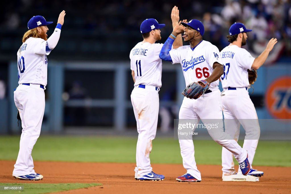 Yasiel Puig #66 of the Los Angeles Dodgers celebrates with Charlie Culberson #37, Logan Forsythe #11 and Justin Turner #10 after defeating the Chicago Cubs in Game One of the National League Championship Series at Dodger Stadium on October 14, 2017 in Los Angeles, California. The Los Angeles Dodgers defeated the Chicago Cubs with a score of 5 to 2.