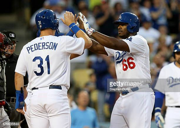 Yasiel Puig of the Los Angeles Dodgers celebrates with Joc Pederson and Alberto Callaspo after all three score on Puig's three run home run in the...