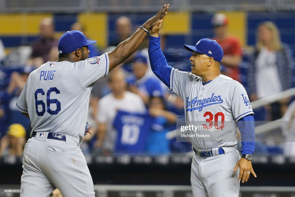 Yasiel Puig #66 of the Los Angeles Dodgers celebrates with manager Dave Roberts #30 after defeating the Miami Marlins 7-0 at Marlins Park on May 17, 2018 in Miami, Florida.