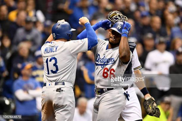 Yasiel Puig of the Los Angeles Dodgers celebrates with Max Muncy after hitting a three run home run against Jeremy Jeffress of the Milwaukee Brewers...