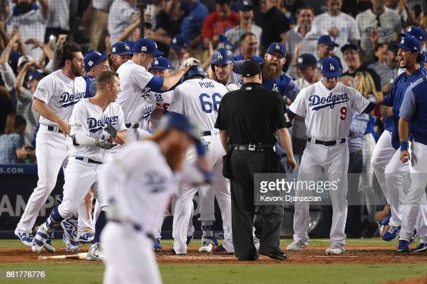 Yasiel Puig of the Los Angeles Dodgers celebrates with teammates as he scores a run after Justin Turner hit a threerun walkoff home run in the ninth...