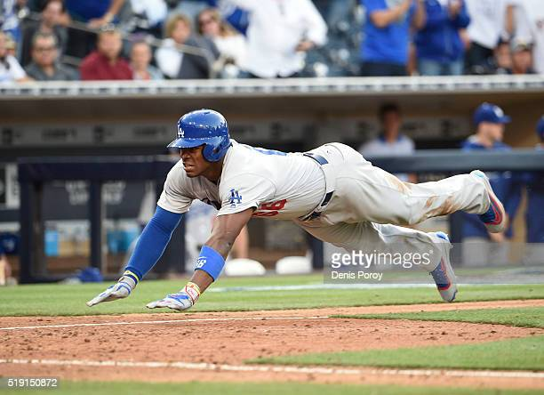 Yasiel Puig of the Los Angeles Dodgers dives as he scores during the eighth inning of a baseball game against the San Diego Padres on opening day at...