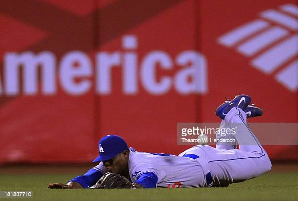 Yasiel Puig of the Los Angeles Dodgers dives but can't make the catch of this ball that goes for an rbi double off the bat of Tony Abreu of the San...