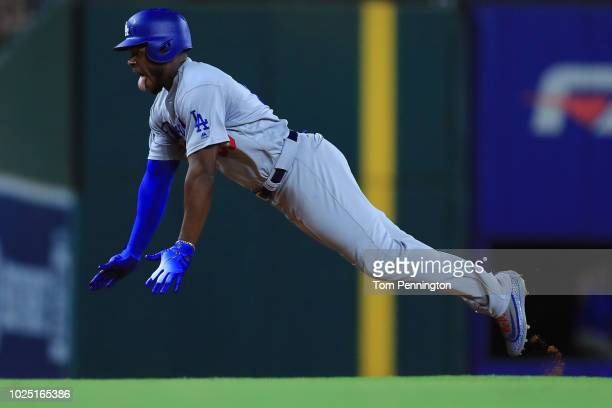 Yasiel Puig of the Los Angeles Dodgers dives into third base after hitting a triple against the Texas Rangers in the top of the seventh inning at...