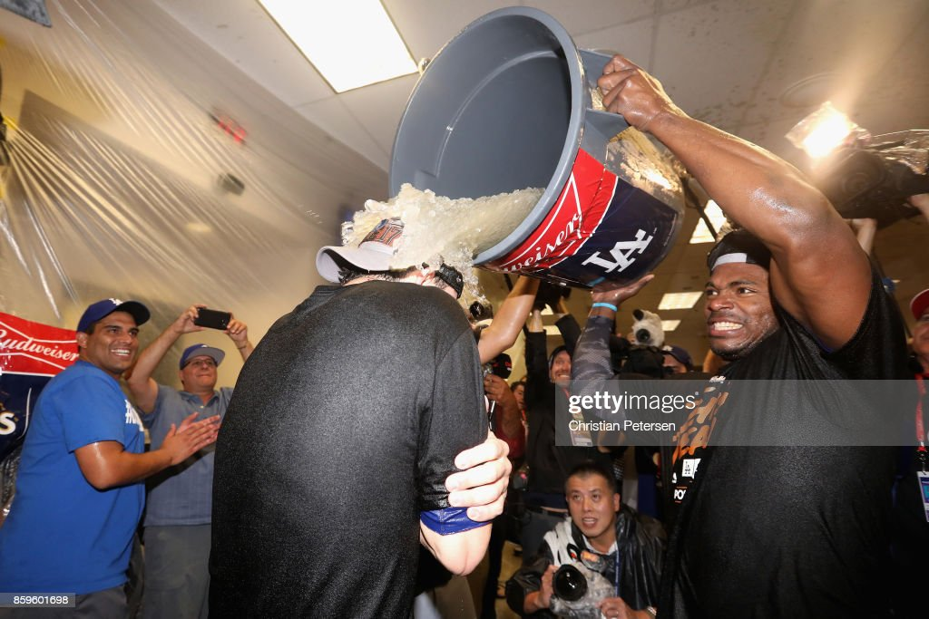 Yasiel Puig #66 of the Los Angeles Dodgers dumps ice on Cody Bellinger #35 in the locker room after defeating the Arizona Diamondbacks 3-1 to win game three of the National League Divisional Series at Chase Field on October 9, 2017 in Phoenix, Arizona.