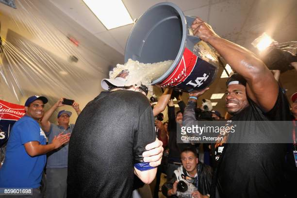 Yasiel Puig of the Los Angeles Dodgers dumps ice on Cody Bellinger in the locker room after defeating the Arizona Diamondbacks 31 to win game three...