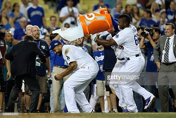 Yasiel Puig of the Los Angeles Dodgers dumps water on Matt Kemp after their 32 win over the St Louis Cardinals in Game Two of the National League...