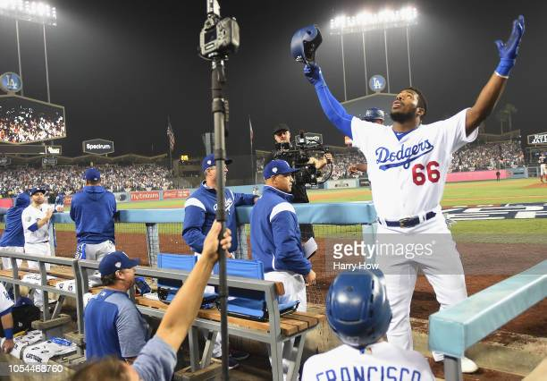 Yasiel Puig of the Los Angeles Dodgers faces and salutes the fans from the dugout after hitting a threerun home run to left field in the sixth inning...
