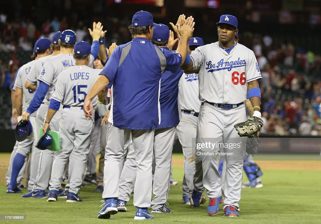 Yasiel Puig #66 of the Los Angeles Dodgers high-fives manager Don Mattingly after defeating the Arizona Diamondbacks in the MLB game at Chase Field on July 8, 2013 in Phoenix, Arizona. The Dodgers defeated the Diamondbacks 6-1.