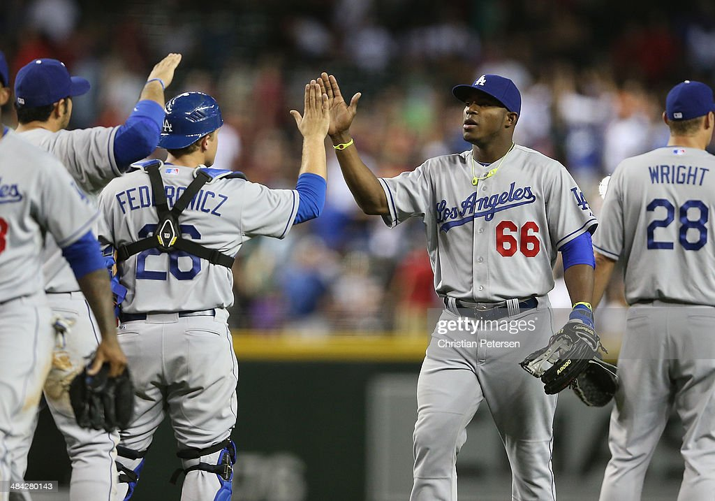 Yasiel Puig #66 of the Los Angeles Dodgers high-fives Tim Federowicz #26 after defeating the Arizona Diamondbacks in the MLB game at Chase Field on April 11, 2014 in Phoenix, Arizona. The Dodgers defeated the Diamondbacks 6-0.