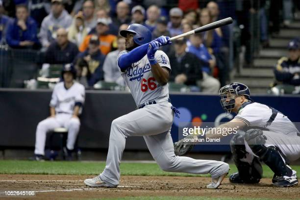 Yasiel Puig of the Los Angeles Dodgers hits a three run home run against Jeremy Jeffress of the Milwaukee Brewers during the sixth inning in Game...