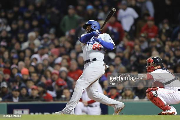 Yasiel Puig of the Los Angeles Dodgers hits an RBI single during the fourth inning against the Boston Red Sox in Game Two of the 2018 World Series at...