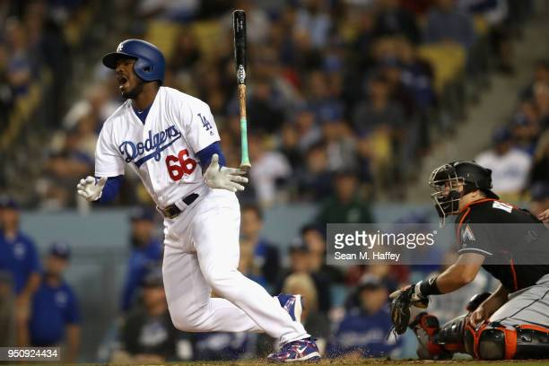 Yasiel Puig of the Los Angeles Dodgers hits into a fielders choice as JT Realmuto of the Miami Marlins looks on during the second inning of a game at...
