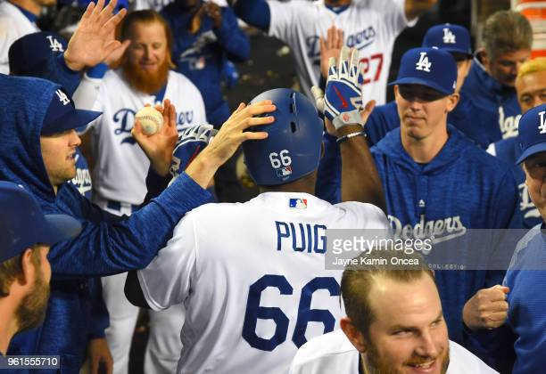 Yasiel Puig of the Los Angeles Dodgers is greeted in the dugout after a solo home run in the sixth inning of the game against the Colorado Rockies at...