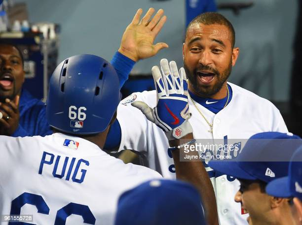 Yasiel Puig of the Los Angeles Dodgers is greeted in the dugout by Matt Kemp of the Los Angeles Dodgers after a solo home run in the sixth inning of...