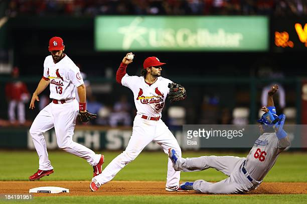 Yasiel Puig of the Los Angeles Dodgers is out at second as Pete Kozma of the St Louis Cardinals turns a double play on a ball hit by Juan Uribe of...