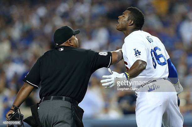 Yasiel Puig of the Los Angeles Dodgers is restrained by home plate umpire Adrian Johnson after Puig was hit by a pitch from Madison Bumgarner of the...