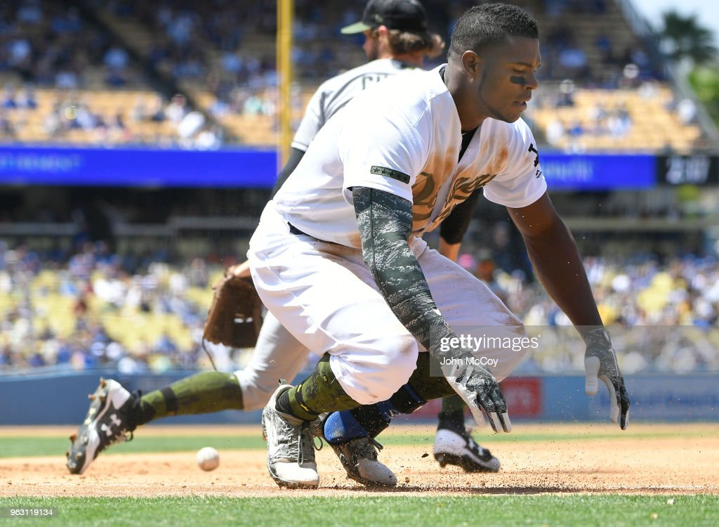 Yasiel Puig #66 of the Los Angeles Dodgers is safe at first base when pitcher Adam Cimber #90 of the San Diego Padres droped the ball at Dodger Stadium on May 27, 2018 in Los Angeles, California.