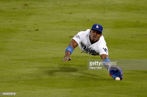 Yasiel Puig of the Los Angeles Dodgers is unable to make a catch on a single hit by David Freese of the St Louis Cardinals in the fifth inning in...