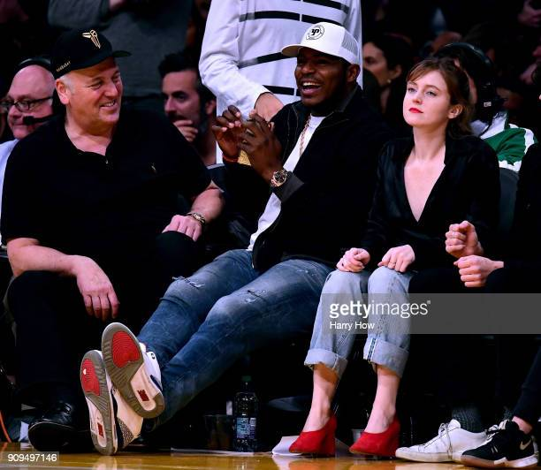 Yasiel Puig of the Los Angeles Dodgers laughs as he sits next to Loraine Nicholson during a 108107 Los Angeles Lakers win over the Boston Celtics at...