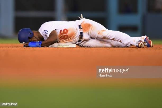 Yasiel Puig of the Los Angeles Dodgers lies on the ground after reaching second base on a sacrifice bunt in the ninth inning against the Chicago Cubs...