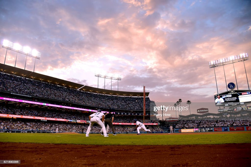 Yasiel Puig #66 of the Los Angeles Dodgers lunges back to first base to beat a throw during the third inning at Dodger Stadium on July 24, 2017 in Los Angeles, California.