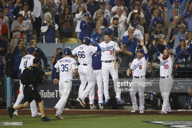 Yasiel Puig of the Los Angeles Dodgers on his way to the dugout with Joc Pederson after Puig hit a threerun home run to left field in the sixth...