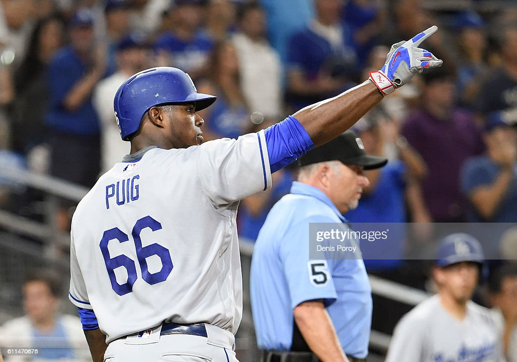 Yasiel Puig #66 of the Los Angeles Dodgers points out to Joc Pederson #31 after scoring during the sixth inning of a baseball game against the San Diego Padres at PETCO Park on September 29, 2016 in San Diego, California.