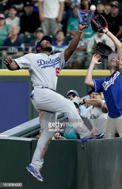 Yasiel Puig of the Los Angeles Dodgers reaches for what would be a missed fly out attempt off a hit by Mitch Haniger of the Seattle Mariners in the...