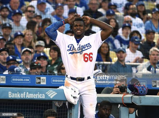 Yasiel Puig of the Los Angeles Dodgers reacts after Yasmani Grandal of struck out against pitcher Hunter Strickland of the San Francisco Giants...