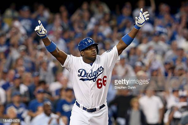 Yasiel Puig of the Los Angeles Dodgers reacts as he hits a RBI triple in the fourth inning against the St Louis Cardinals in Game Three of the...