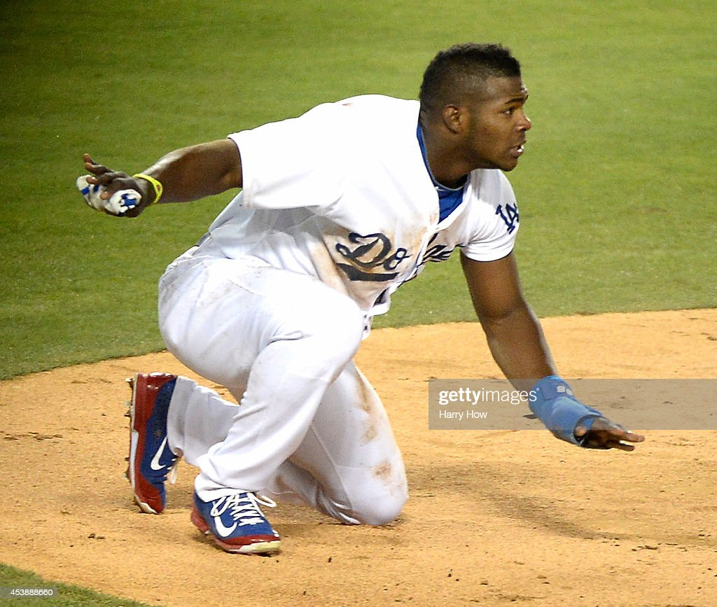 Yasiel Puig #66 of the Los Angeles Dodgers reacts to his slide home to score a run to trail 3-1 to the San Diego Padres during the third inning at Dodger Stadium on August 20, 2014 in Los Angeles, California.