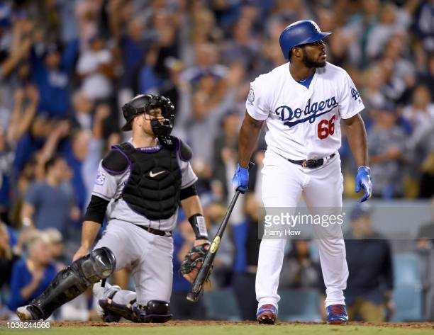Yasiel Puig of the Los Angeles Dodgers reacts to his three run homerun in front of Chris Iannetta of the Colorado Rockies to take a 52 lead during...