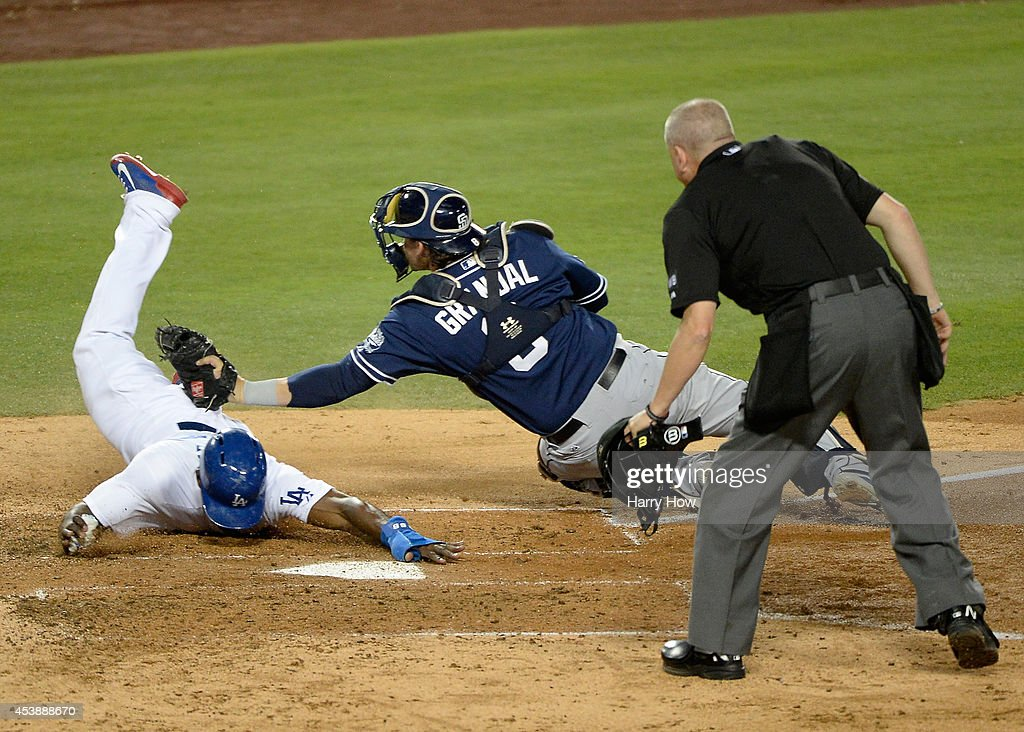 Yasiel Puig #66 of the Los Angeles Dodgers slides around the tag of Yasmani Grandal #8 of the San Diego Padres to score a run and trail 3-1 during the third inning at Dodger Stadium on August 20, 2014 in Los Angeles, California.