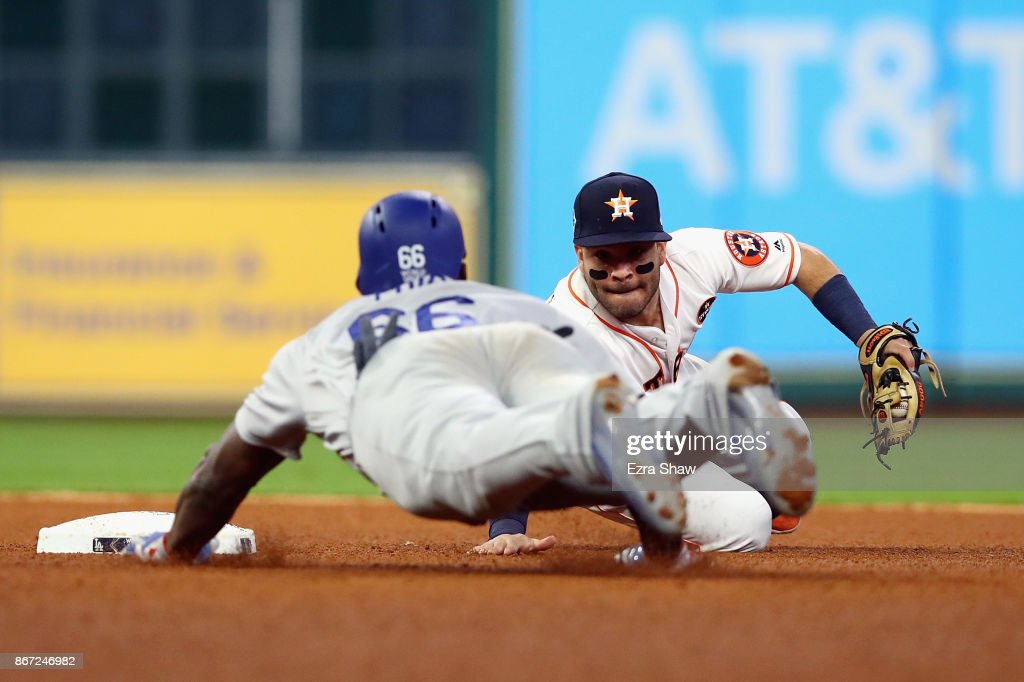 Yasiel Puig #66 of the Los Angeles Dodgers slides in to second and is tagged out by Jose Altuve #27 of the Houston Astros during the fourth inning in game three of the 2017 World Series at Minute Maid Park on October 27, 2017 in Houston, Texas.