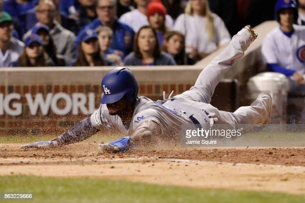 Yasiel Puig of the Los Angeles Dodgers slides into home plate to score a run in the fourth inning against the Chicago Cubs during game five of the...