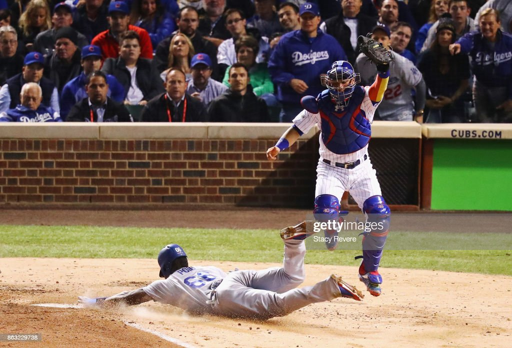 Yasiel Puig #66 of the Los Angeles Dodgers slides into home plate to score a run past Willson Contreras #40 of the Chicago Cubs in the fourth inning during game five of the National League Championship Series at Wrigley Field on October 19, 2017 in Chicago, Illinois.