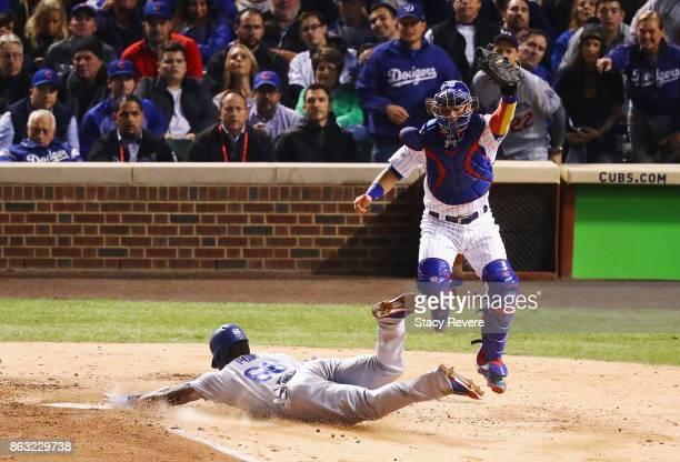 Yasiel Puig of the Los Angeles Dodgers slides into home plate to score a run past Willson Contreras of the Chicago Cubs in the fourth inning during...