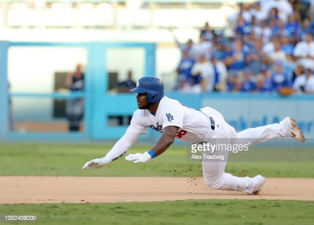 Yasiel Puig of the Los Angeles Dodgers slides into second base after hitting a double in the eighth inning of Game 5 of the NLCS against the...